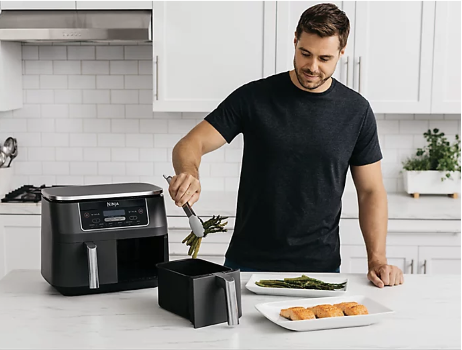 Model taking food out of a black two drawer air fryer with digital display