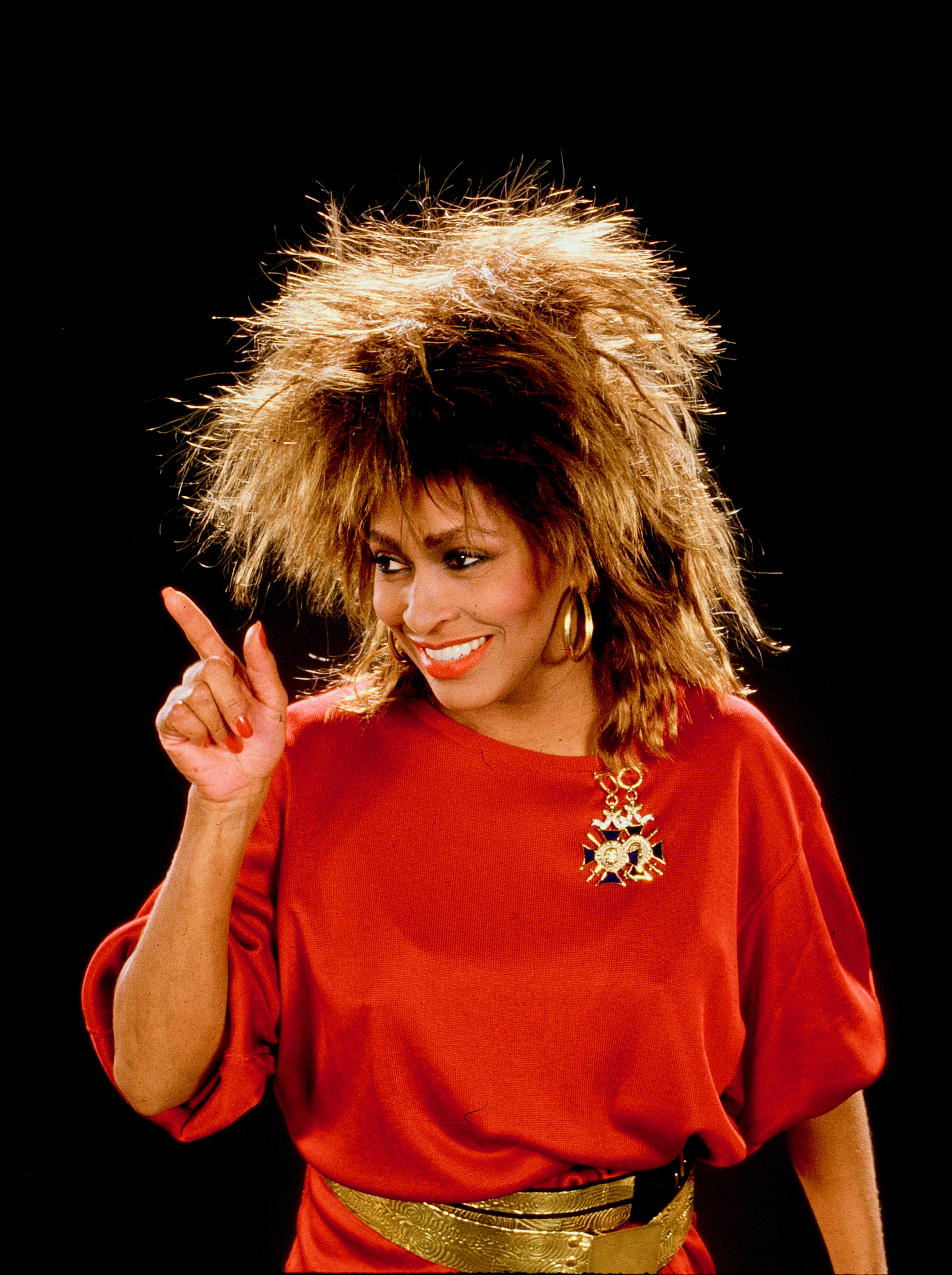 Tina Turner posing in red dress 1985