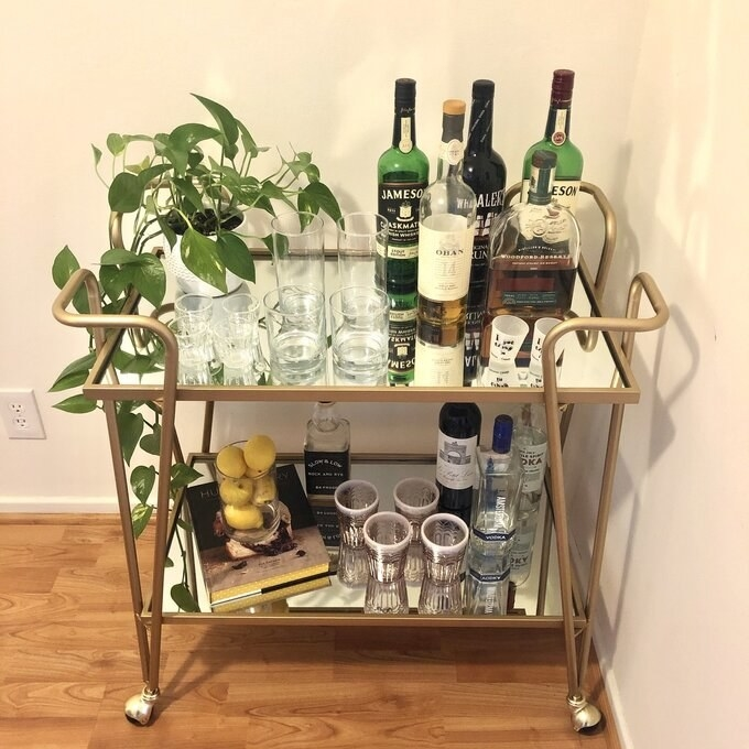 a reviewer's photo of the bar cart with glasses and accessories