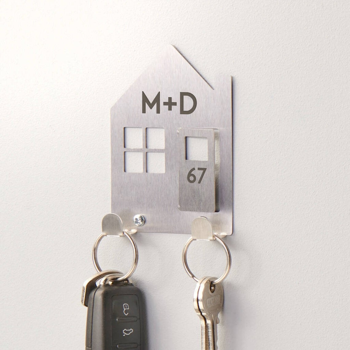 Flat metal double hook in the shape of a house. It has two initials and a door number.