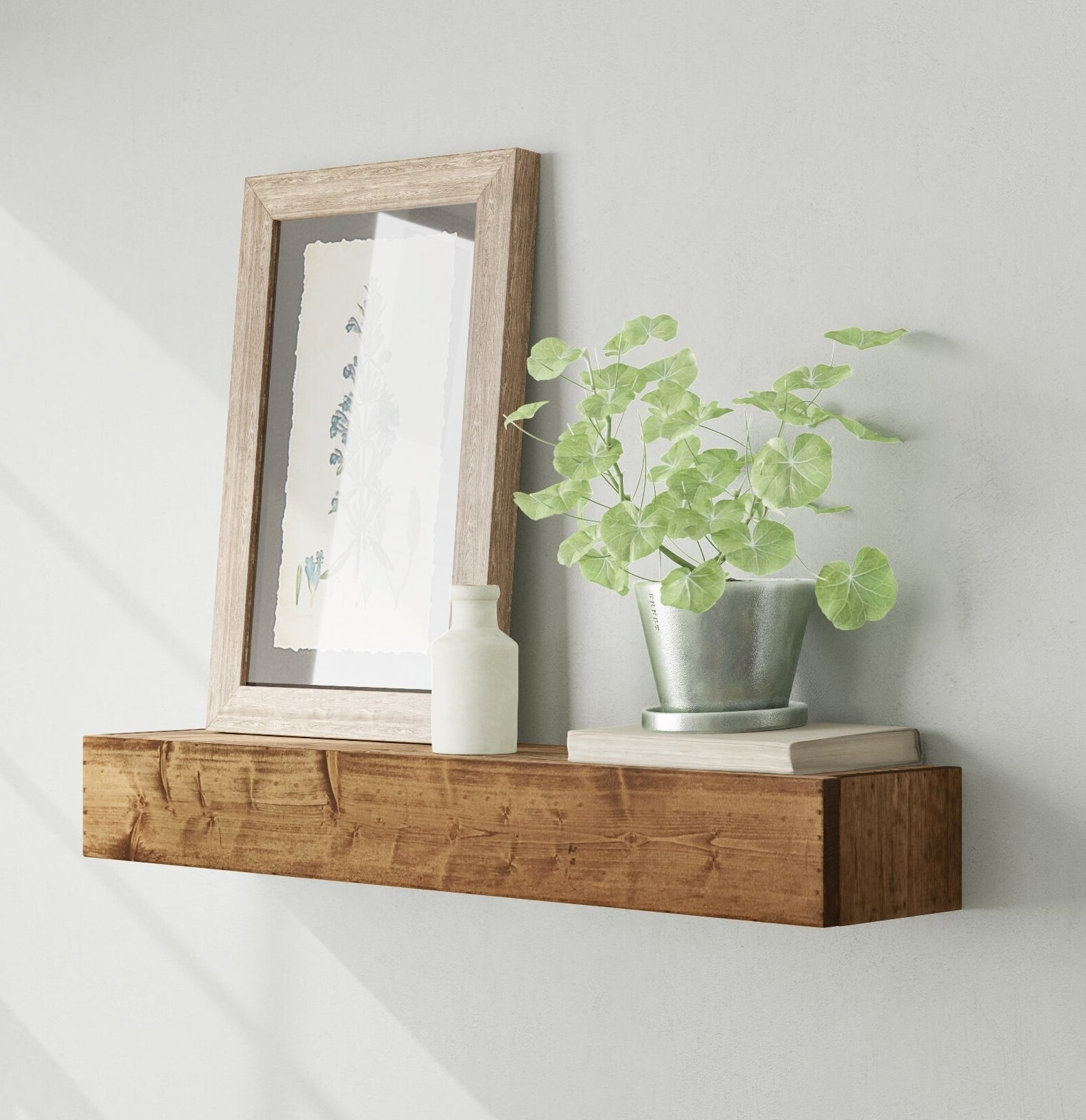 The shelf with a framed photo and plant on top