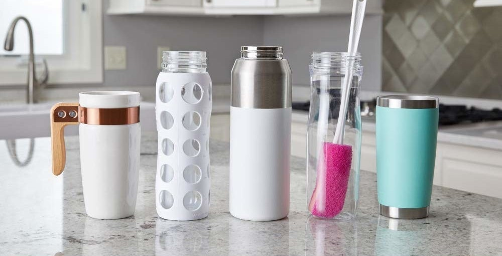 Different types of bottles and the brush kept on a kitchen counter.