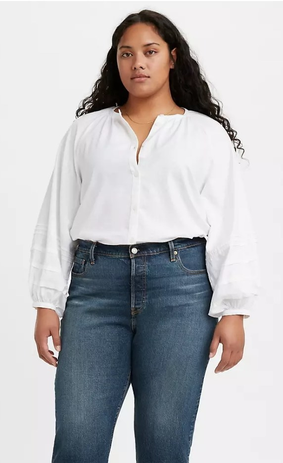 Model wearing white puff-sleeve top with blue jeans