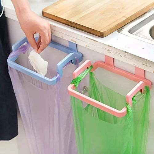 A person disposing used tissues in a garbage bag. The bag is attached to a holder which in turn is attached to a cabinet door.