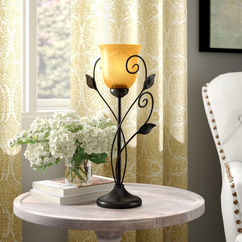 The lamp, which has iron vines crawling up the side to make the bulb look like a flower