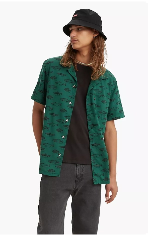 Model wearing green button down shirt with fish print over black shirt with black pants