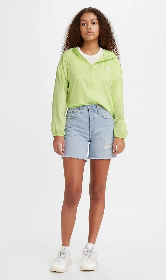 Model wearing light wash denim mid-thigh shorts with green jacket
