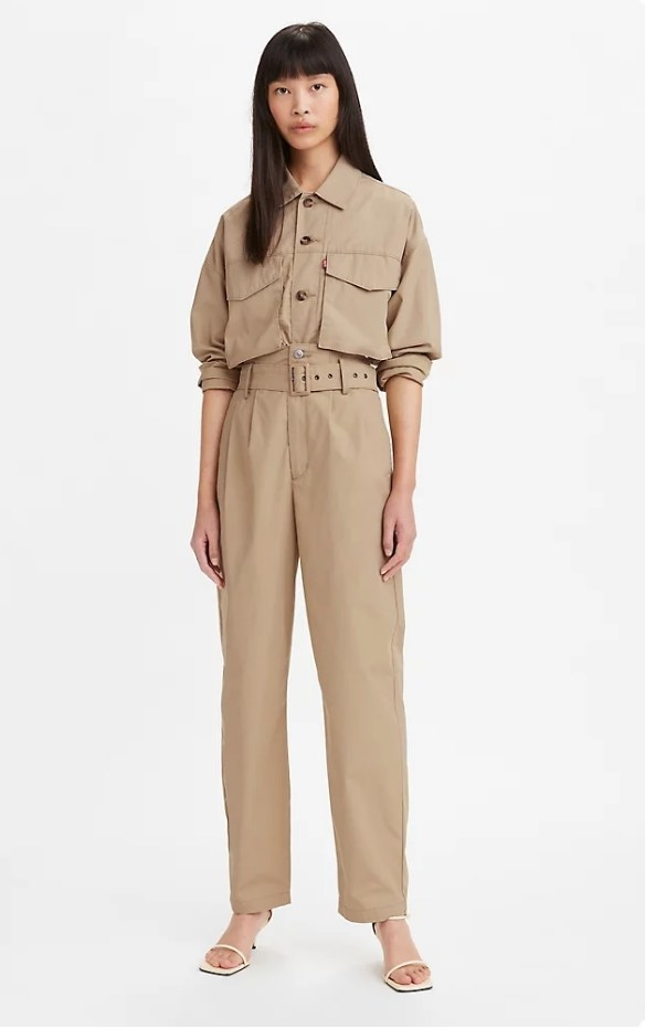 Model wearing tan pleated pants with matching top