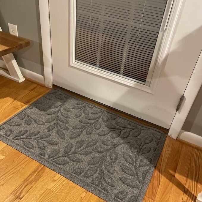 a reviewer's gray door mat placed in front of the front door