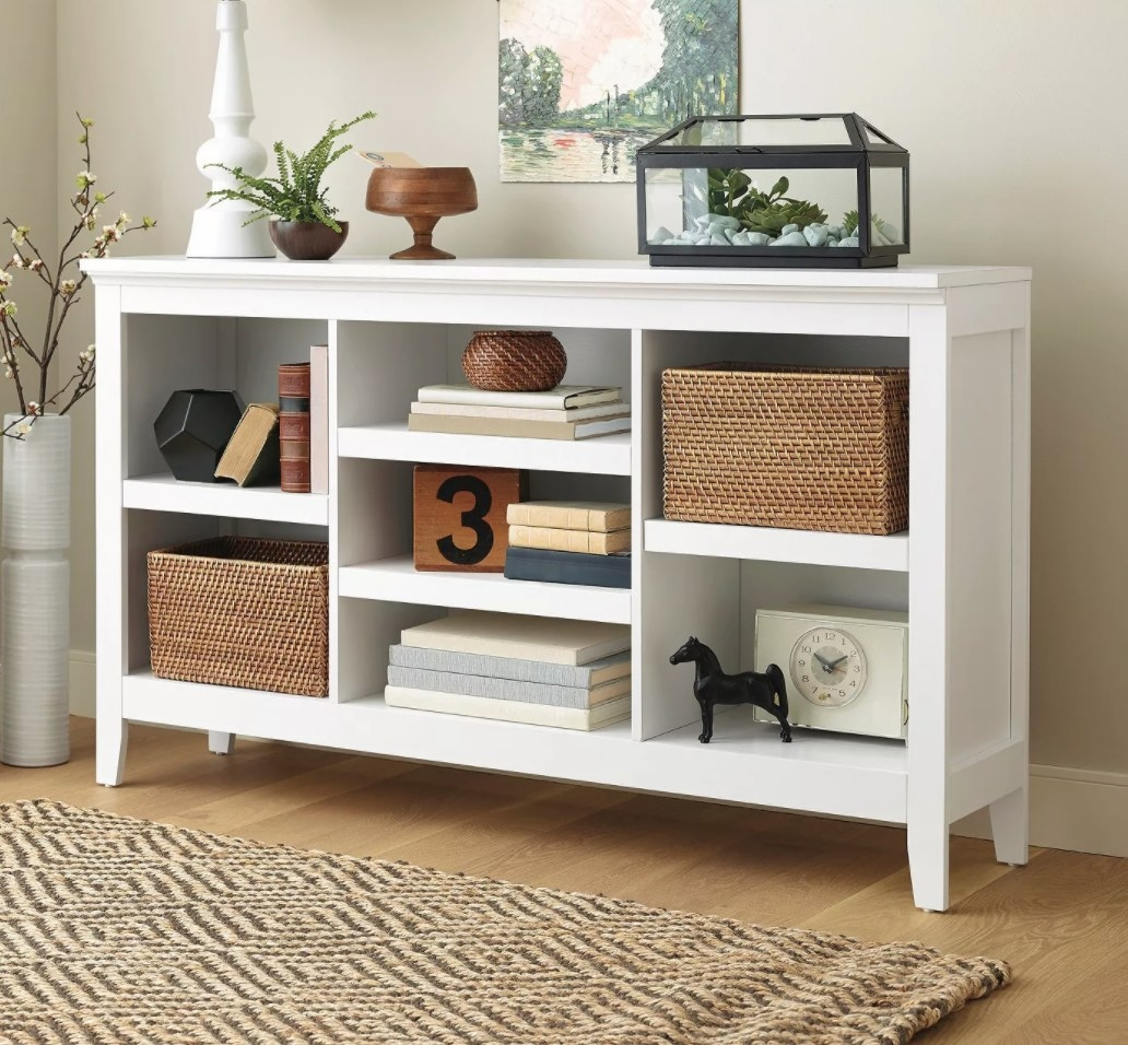 A white wooden horizontal bookcase with seven open shelves