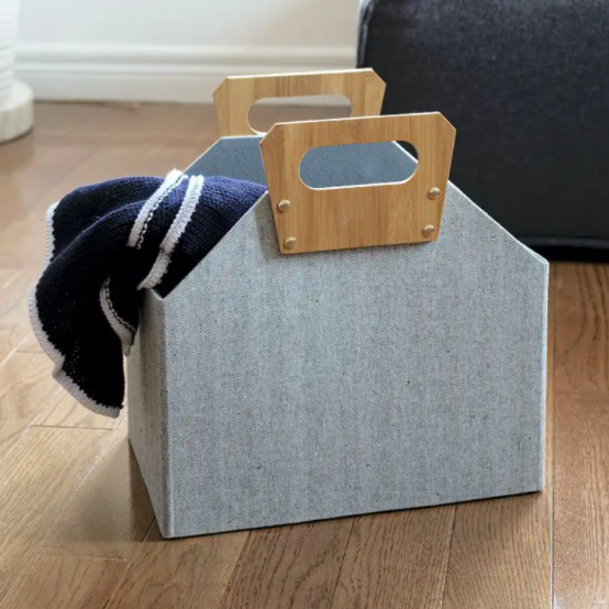 The folding storage bin with a blanket peeking out the edge
