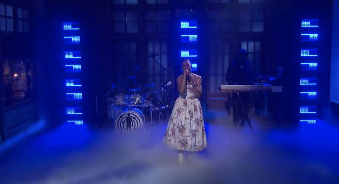 Kid Cudi performs while wearing a long floral-print, spaghetti-strap gown
