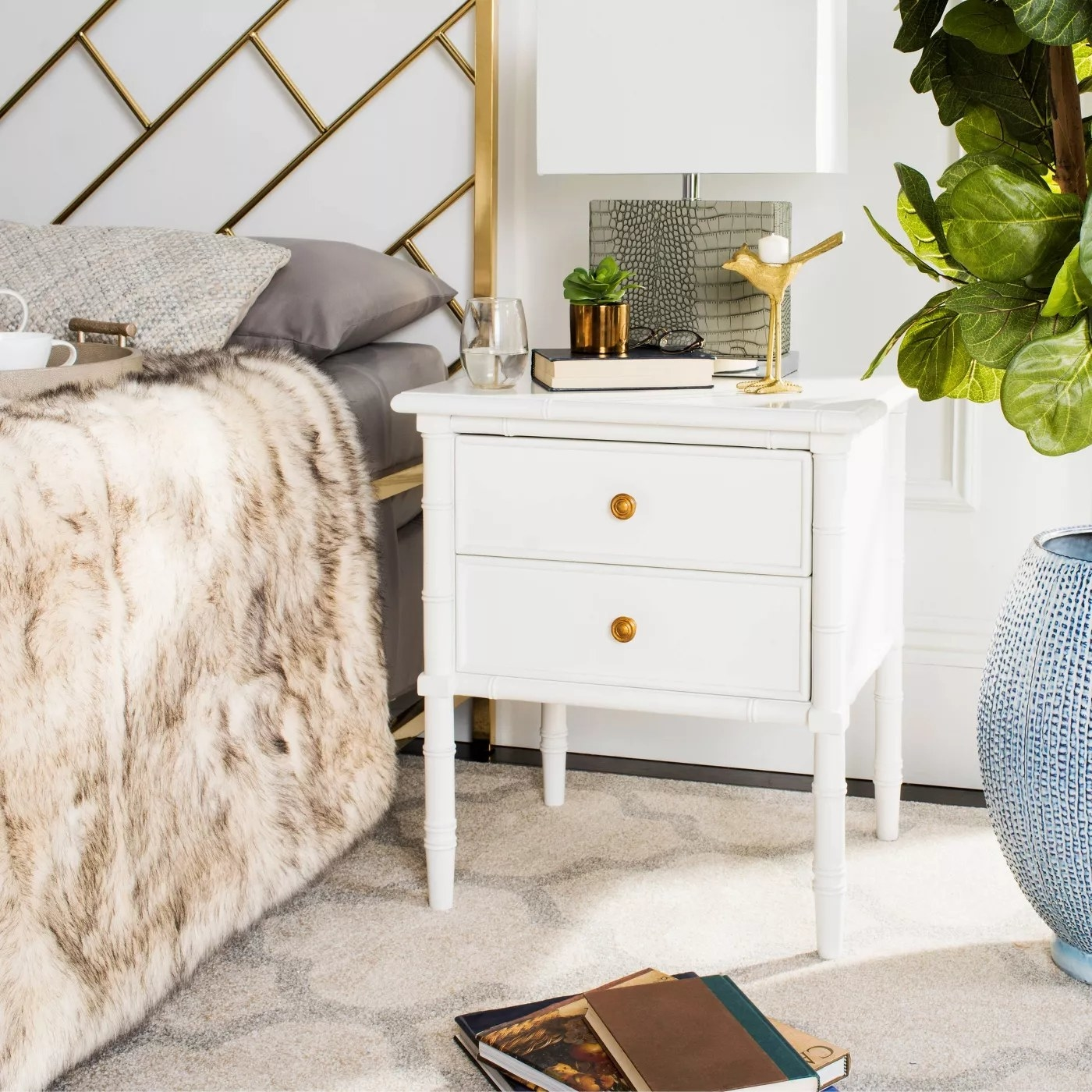 The white nightstand with gold handles