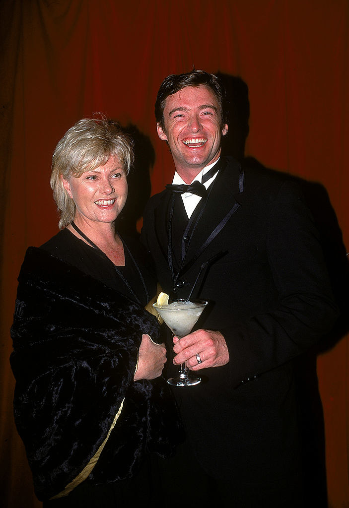 Hugh holding a drink as she smiles with Deborra