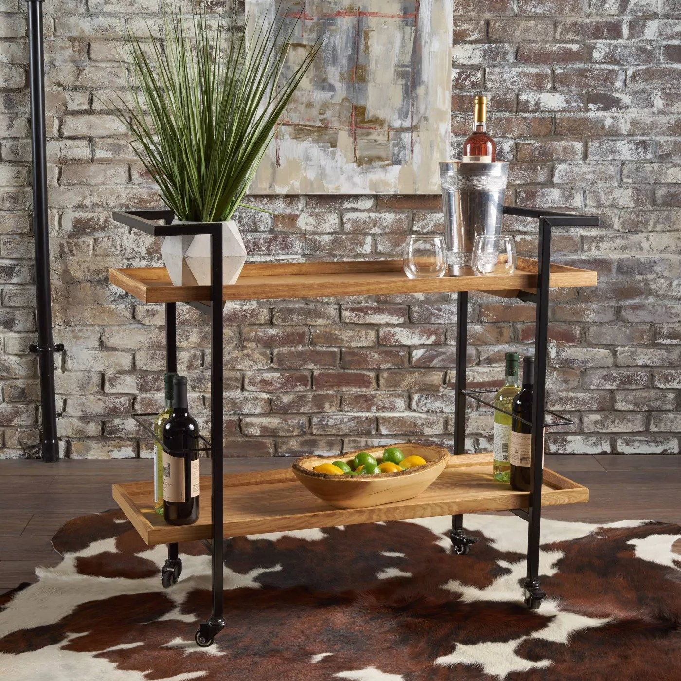 A rolling bar cart with natural shelves and an iron frame