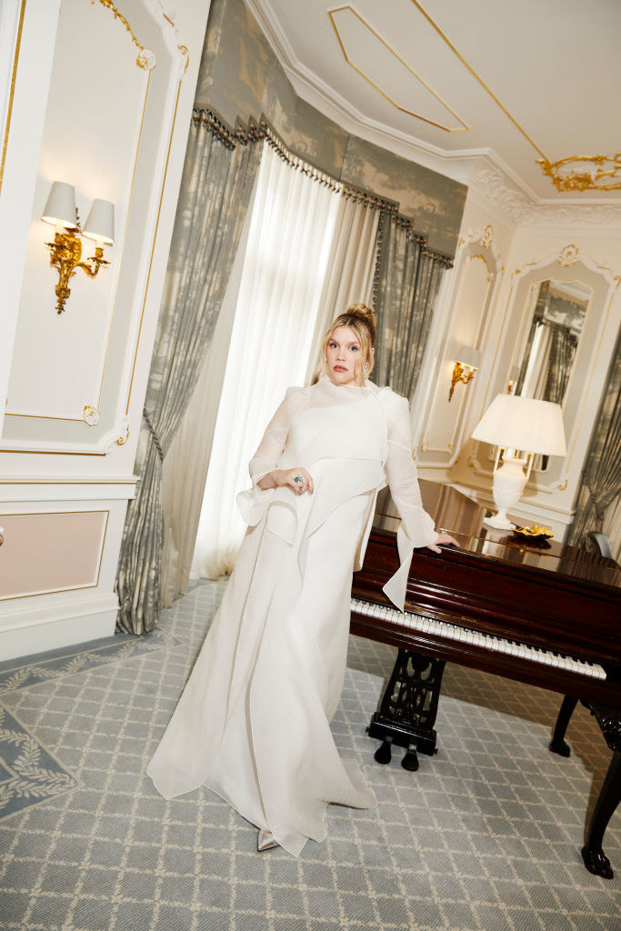 Emerald standing by a piano and wearing a long-sleeved, high-necked white gown
