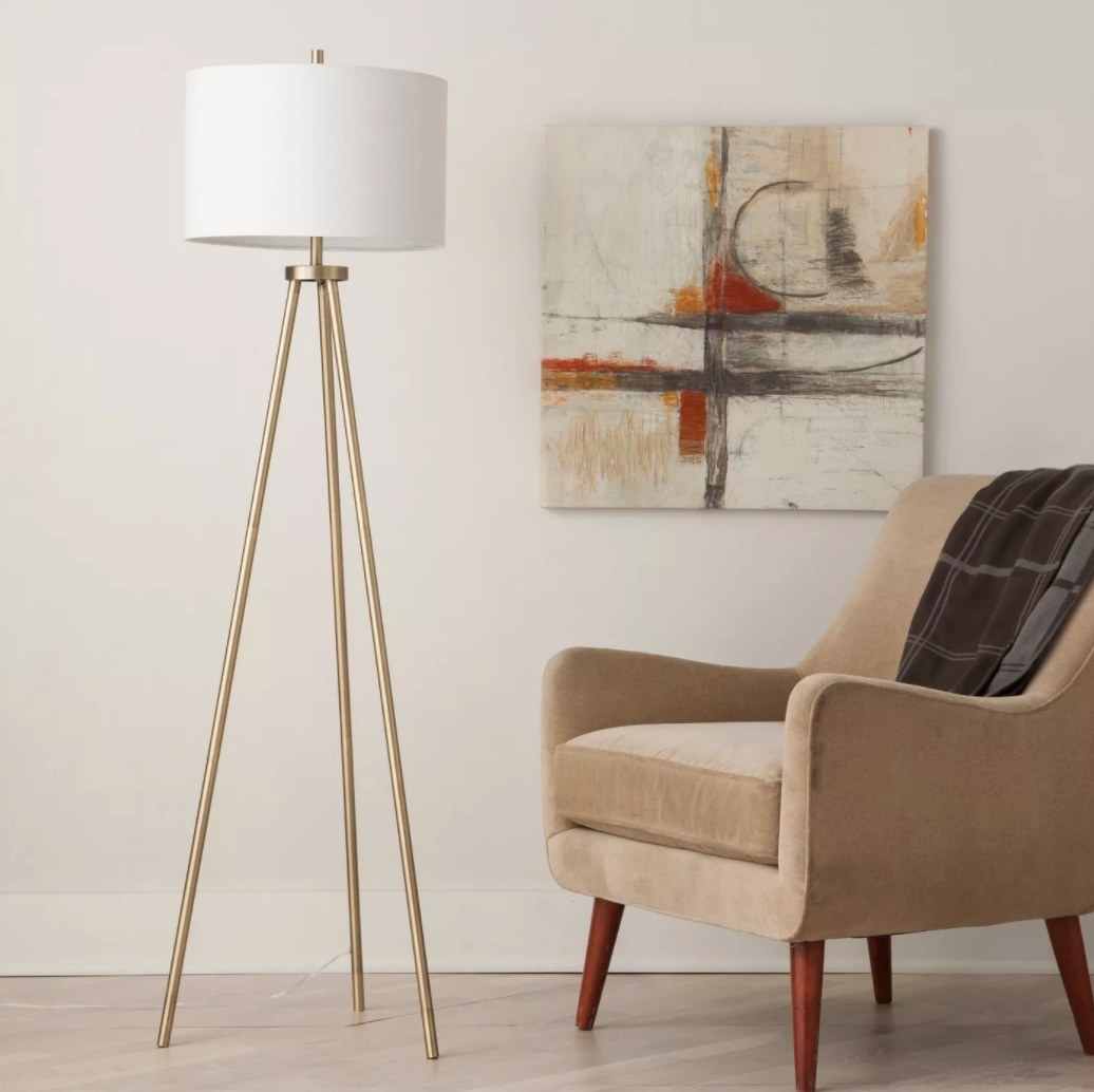 A tripod floor lamp with brass legs and white fabric lampshade