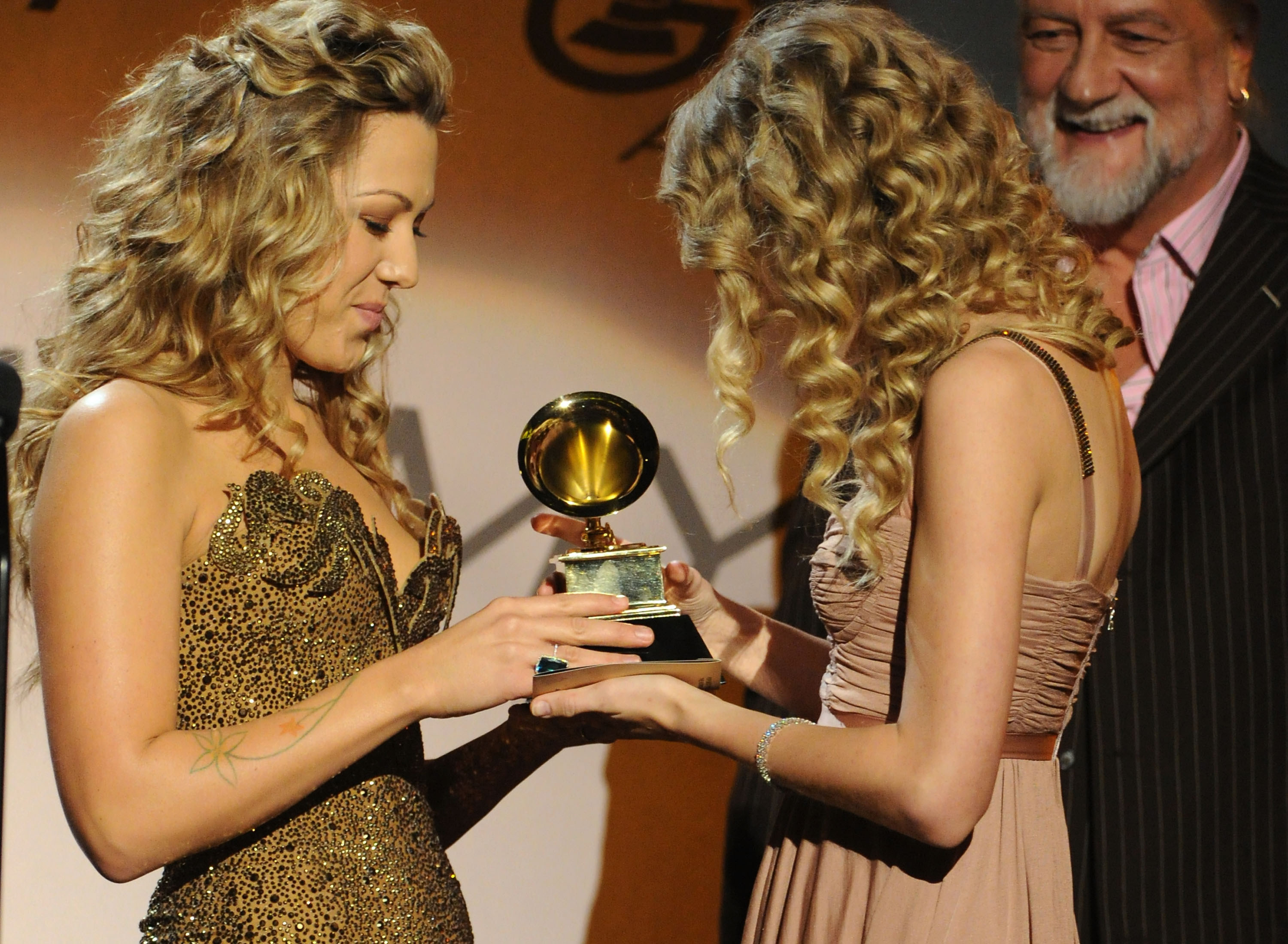 Colbie Caillat and Taylor Swift onstage at an awards ceremony
