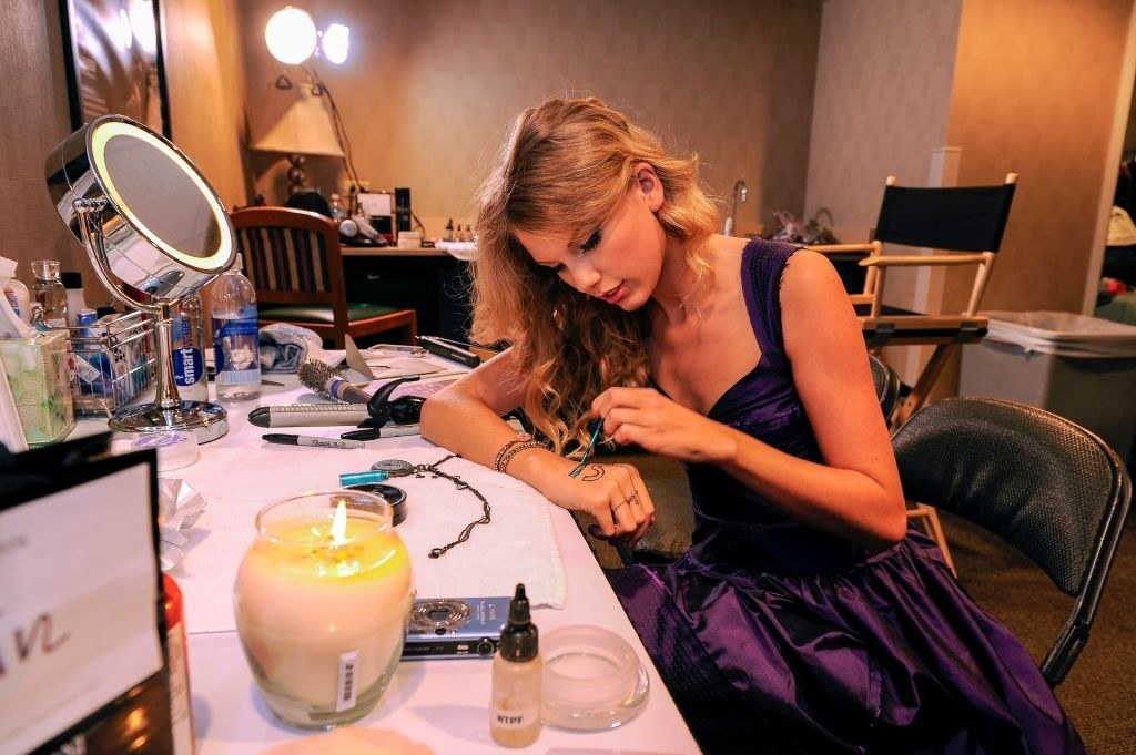 Taylor sitting at a table painting 13 on her hand, with a burning candle and wearing a gown