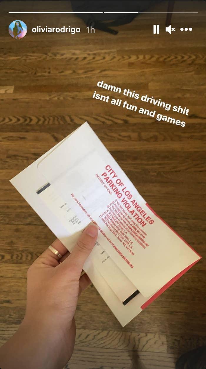 Olivia Rodrigo holding a parking ticket