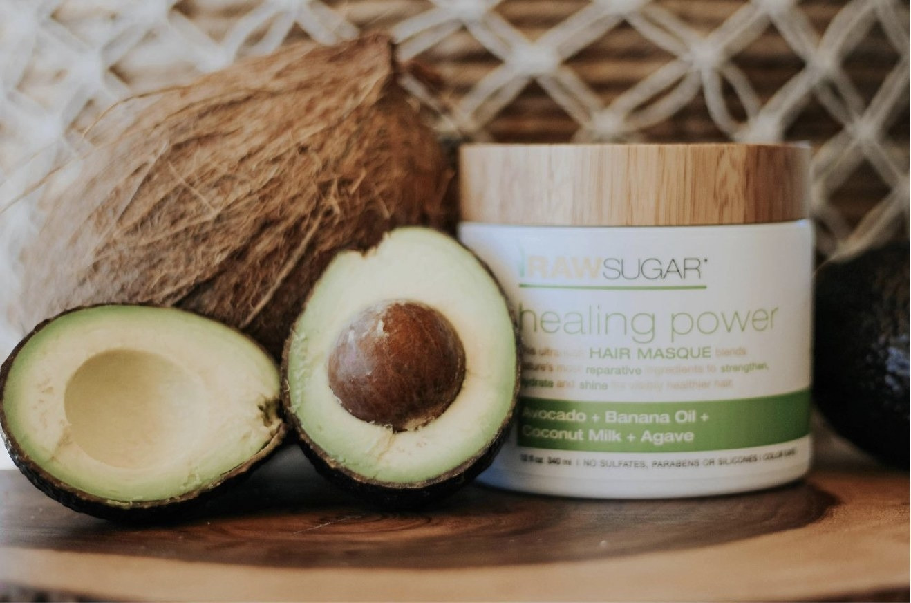 A jar of hair mask with a cut avocado