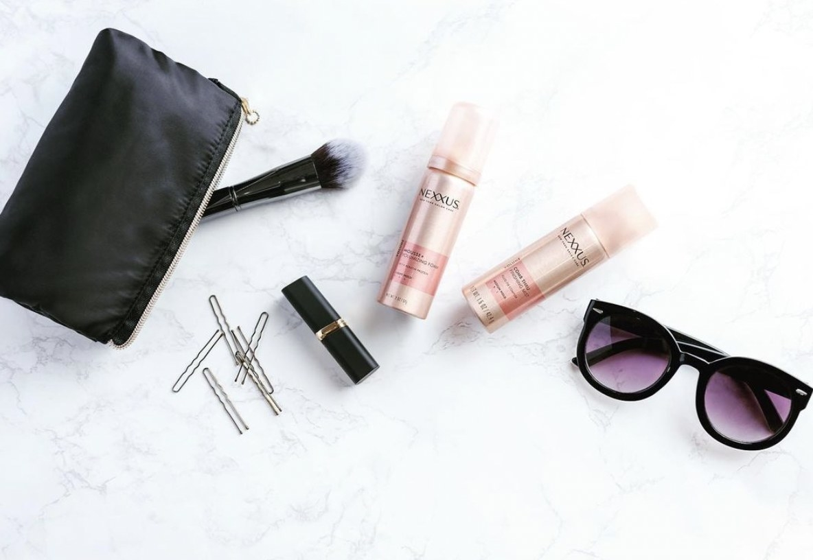 A black purse with a fluffy makeup brush, hair pins, lipstick, sunglasses and two cans of hairspray and hair mousse