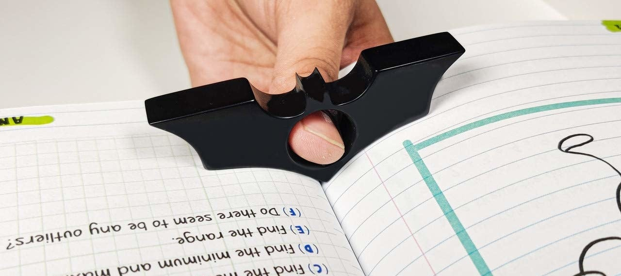 A person holding a book open with the Batman holder.