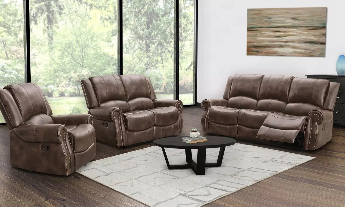 The three-piece reclining sofa set in brown around a black coffee table