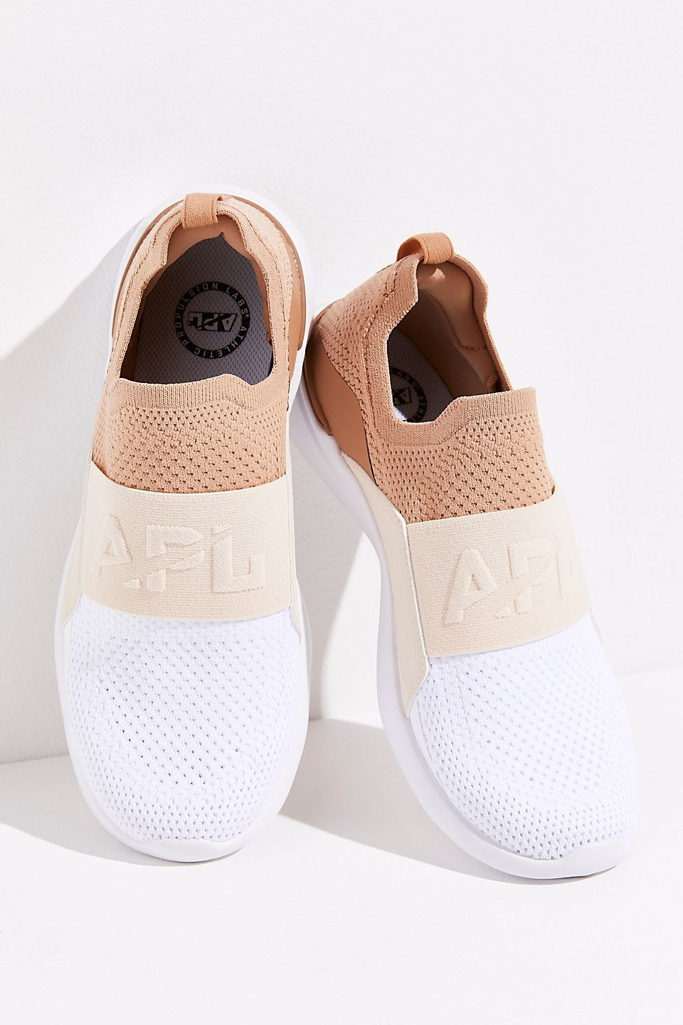 """white and orange knit sneakers with peach band across the top of the foot with the letters """"APL"""" in it"""