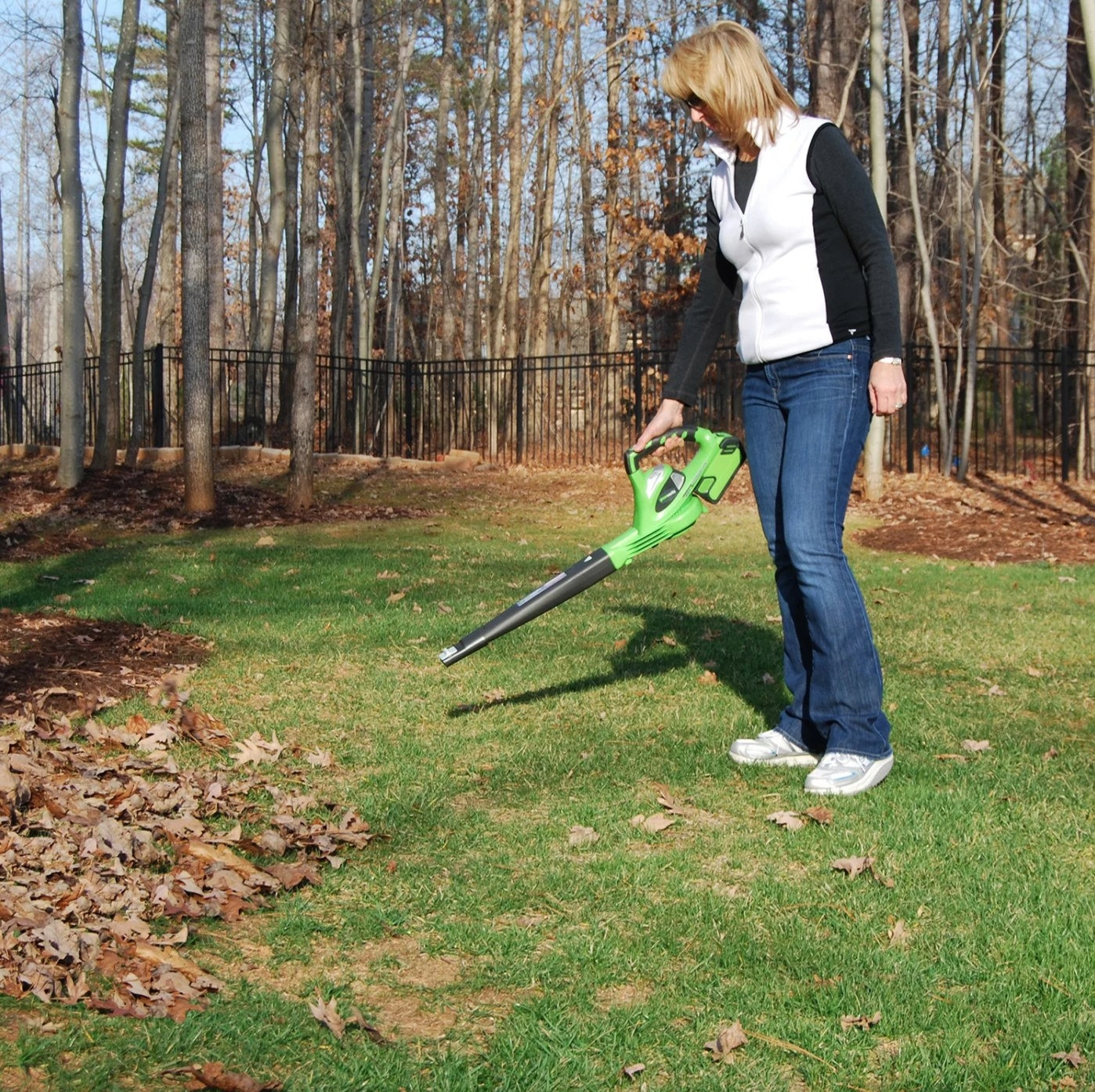 The lawn blower in lime green being held by a model blowing leaves