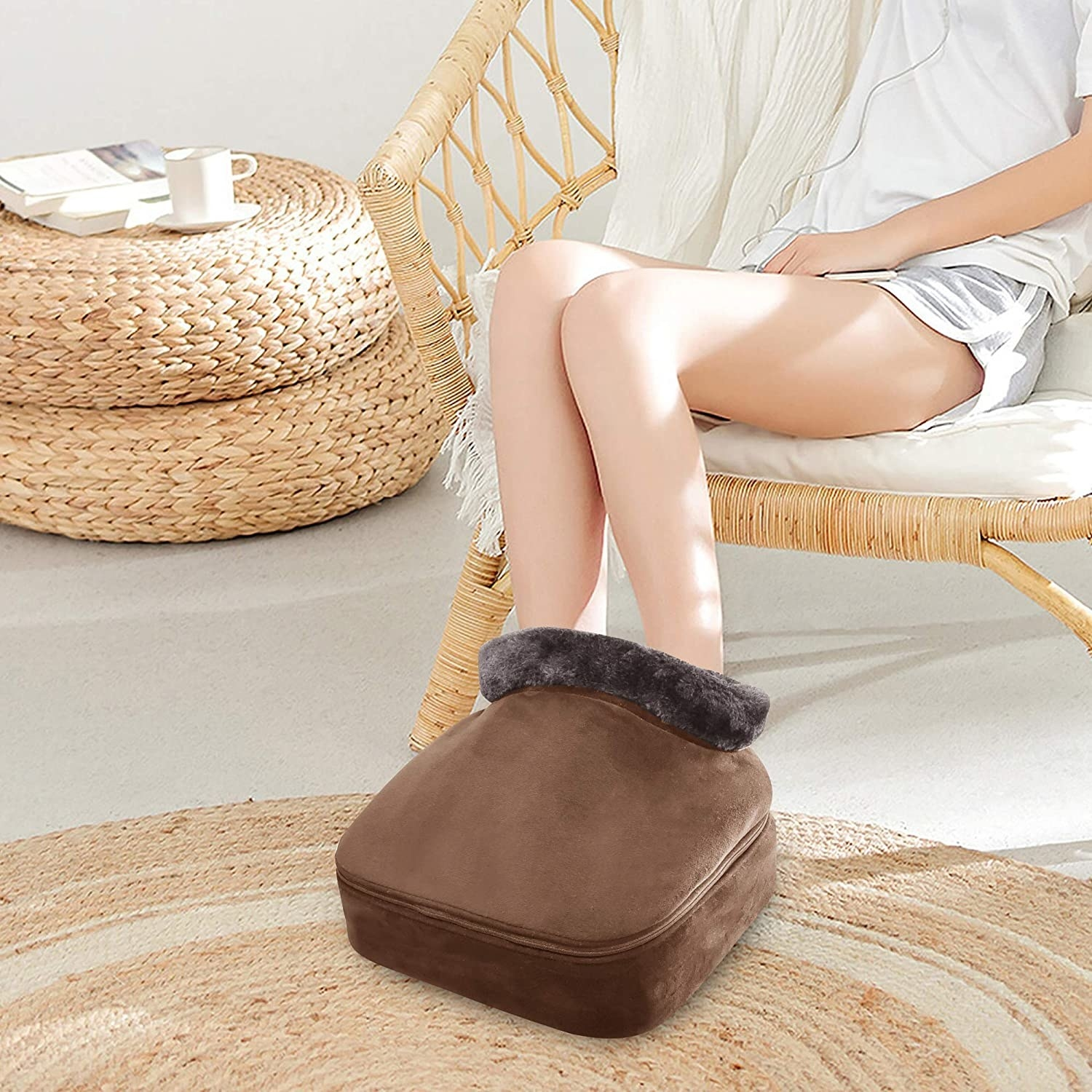 person using a brown foot warmer and massager while sitting in a chair
