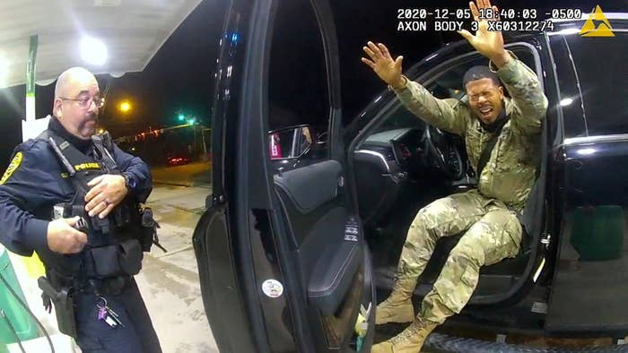 Nazario's eyes are closed in response to being pepper-prayed and he has his arms raised as he sits in the driver's seat of the car with the door open. A police officer stands on the other side of the door.