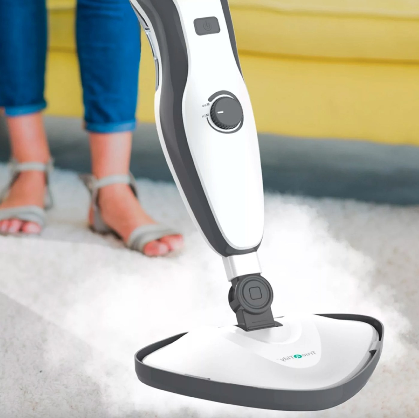 The heavy-duty steam mop in white with black detailing being used by a model on a rug