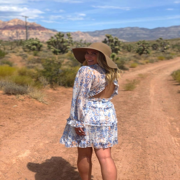 another reviewer wears the A1 white Dokotoo ruffled mini dress on a dirt path