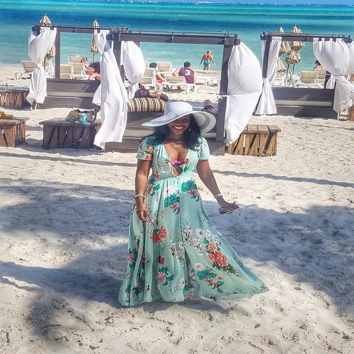 image of reviewer wearing the A green milumia floral maxi dress at a sandy beach resort