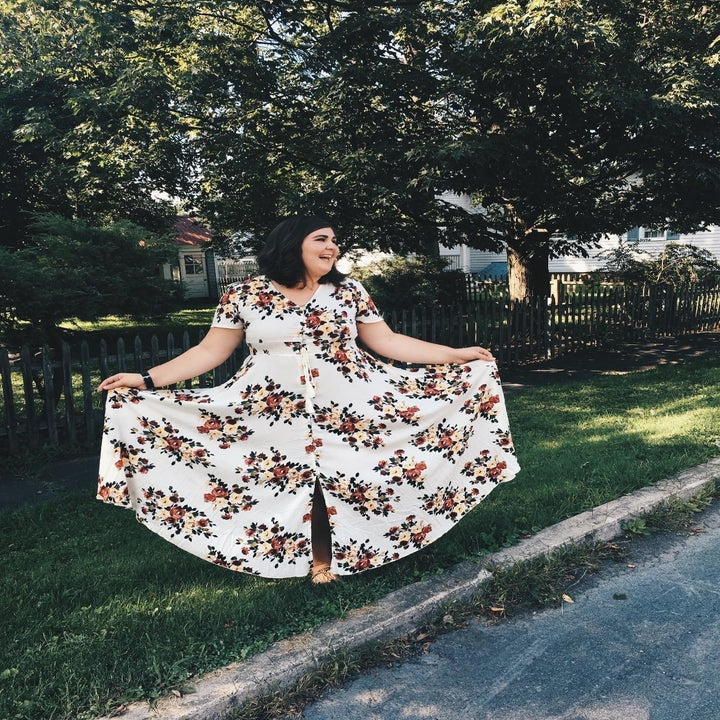 image of plus size reviewer wearing the white floral milumia button up maxi dress on a tree-lined street