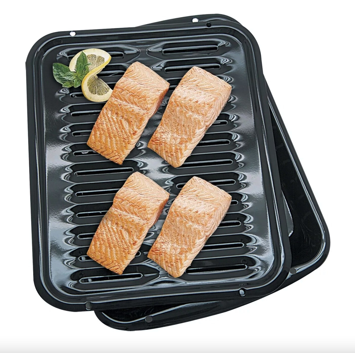 The five-piece pan set in black holding fillets of salmon, a slice of lemon, and mint