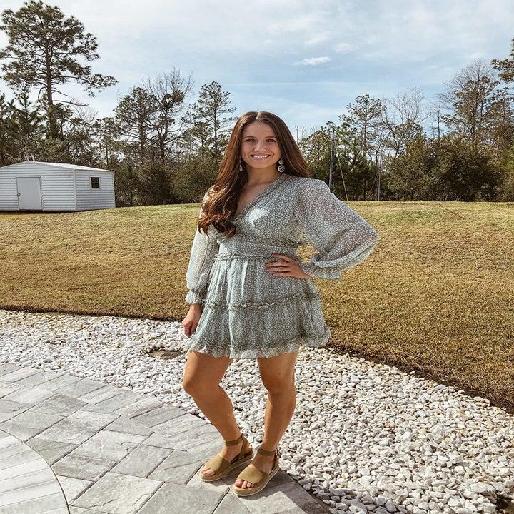 a reviewer wears the A2 green Dokotoo ruffled mini dress outdoors