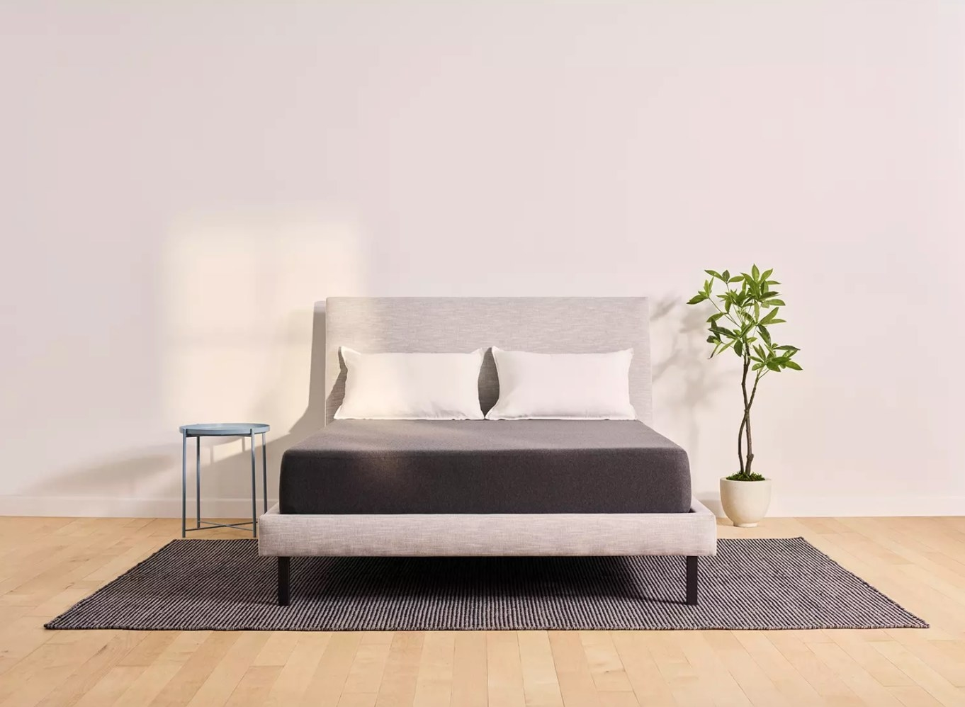 The Casper full mattress hold a gray fabric bed frame with a headboard