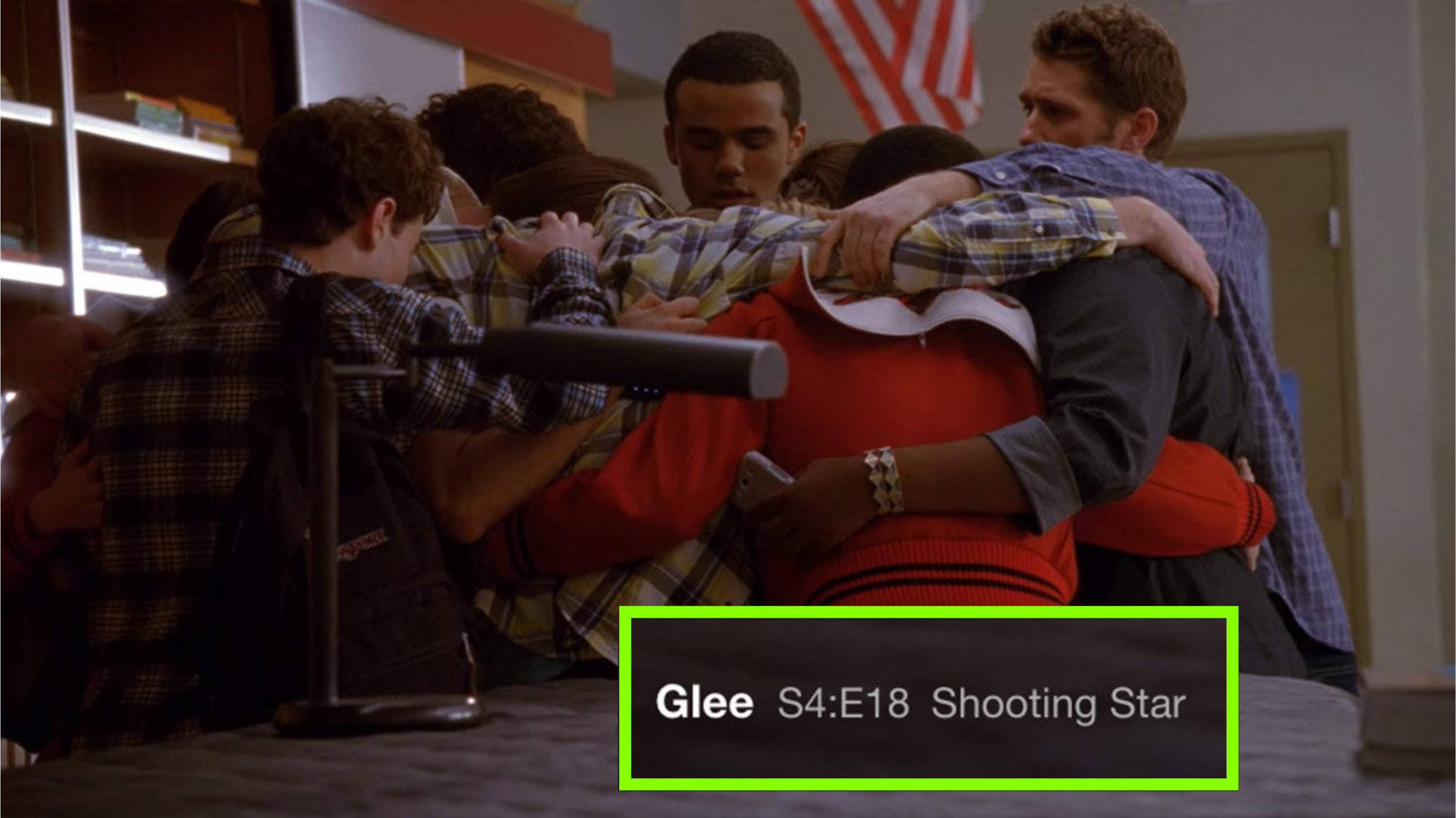 """The glee club huddling and comforting each other in the choir room; a screenshot of the episode title, """"Shooting Star,"""" in the lower righthand corner"""