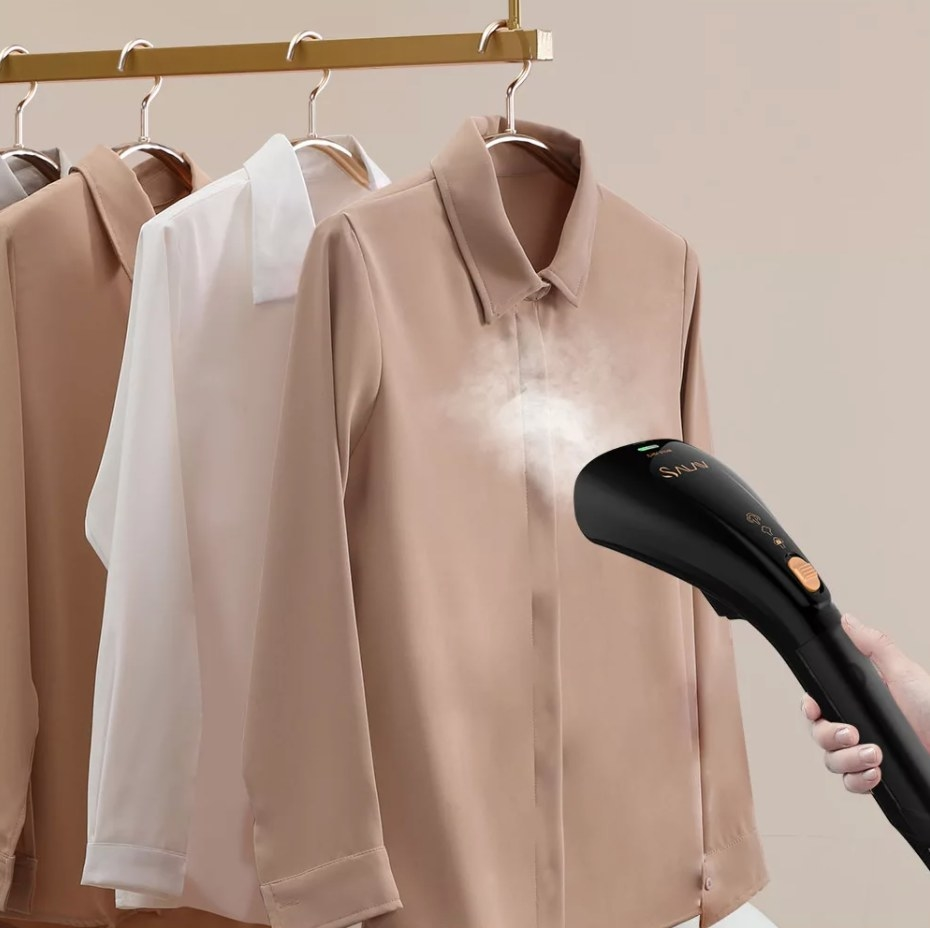 The handheld steamer in black being used on a series of nude colored shirts