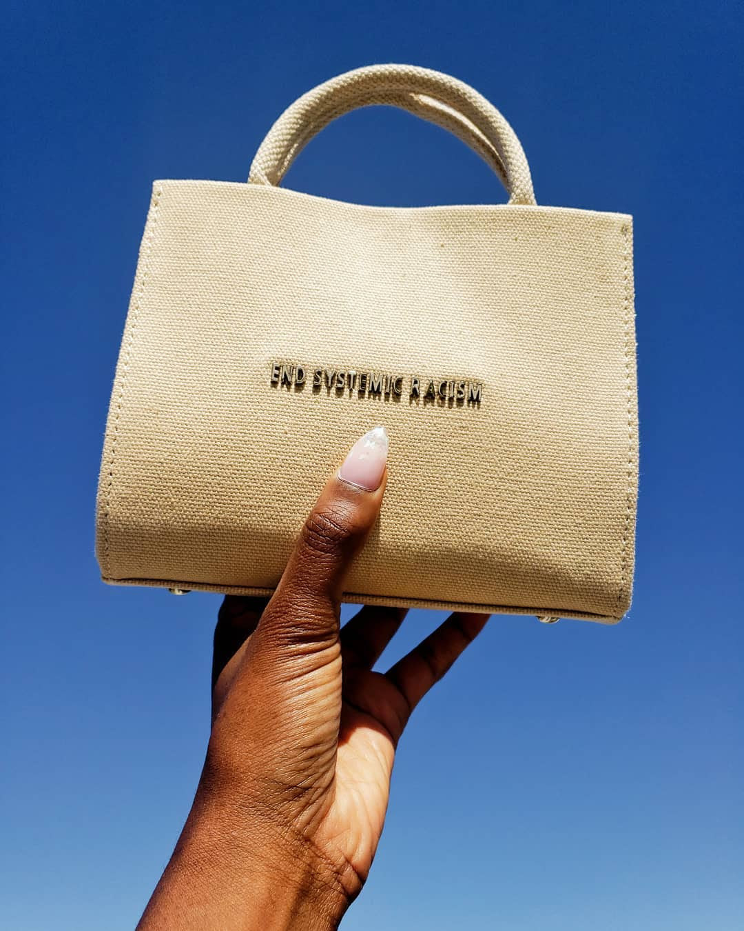 """buzzfeed editor holding a small, square tan bag reading """"End Systematic Racism"""" in small metal letters on the front"""