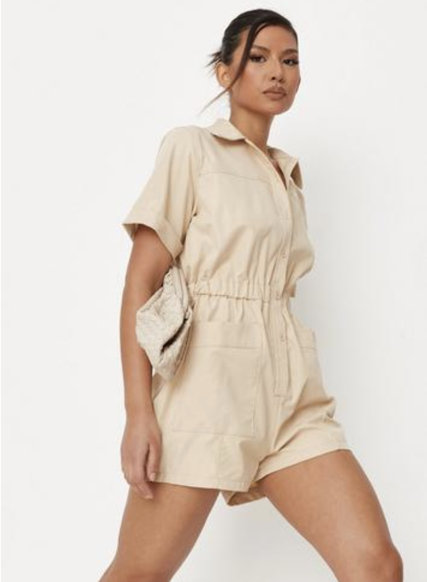 Model in ivory/beige jumpsuit with shorts and short-sleeve length, cinched at the waist with elastic