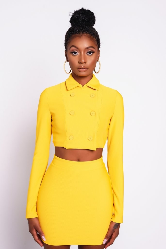 Model in a yellow cropped front buttoned collared jacket styled like Cher in Clueless