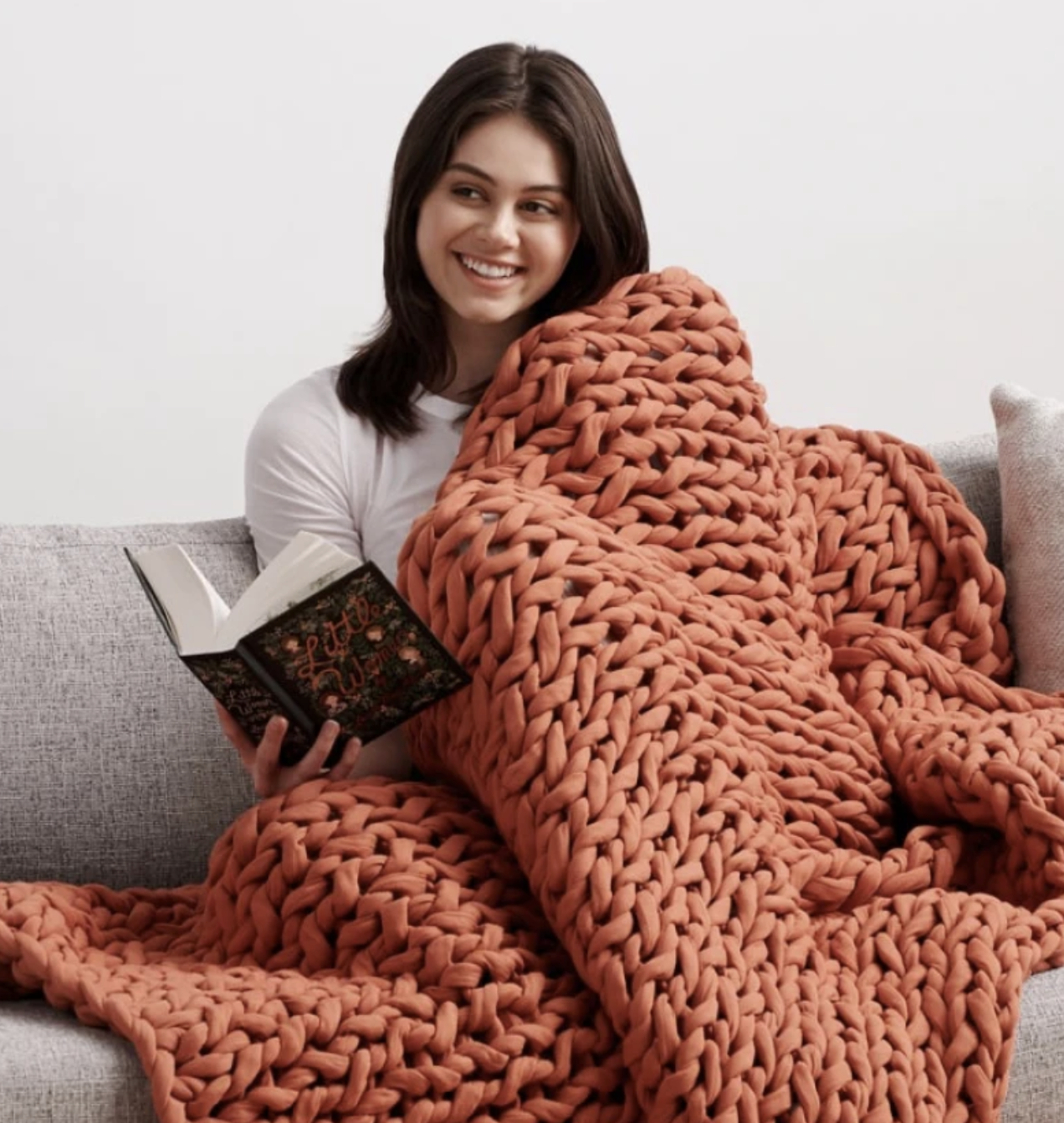 Model snuggled under the blanket with a book on the couch