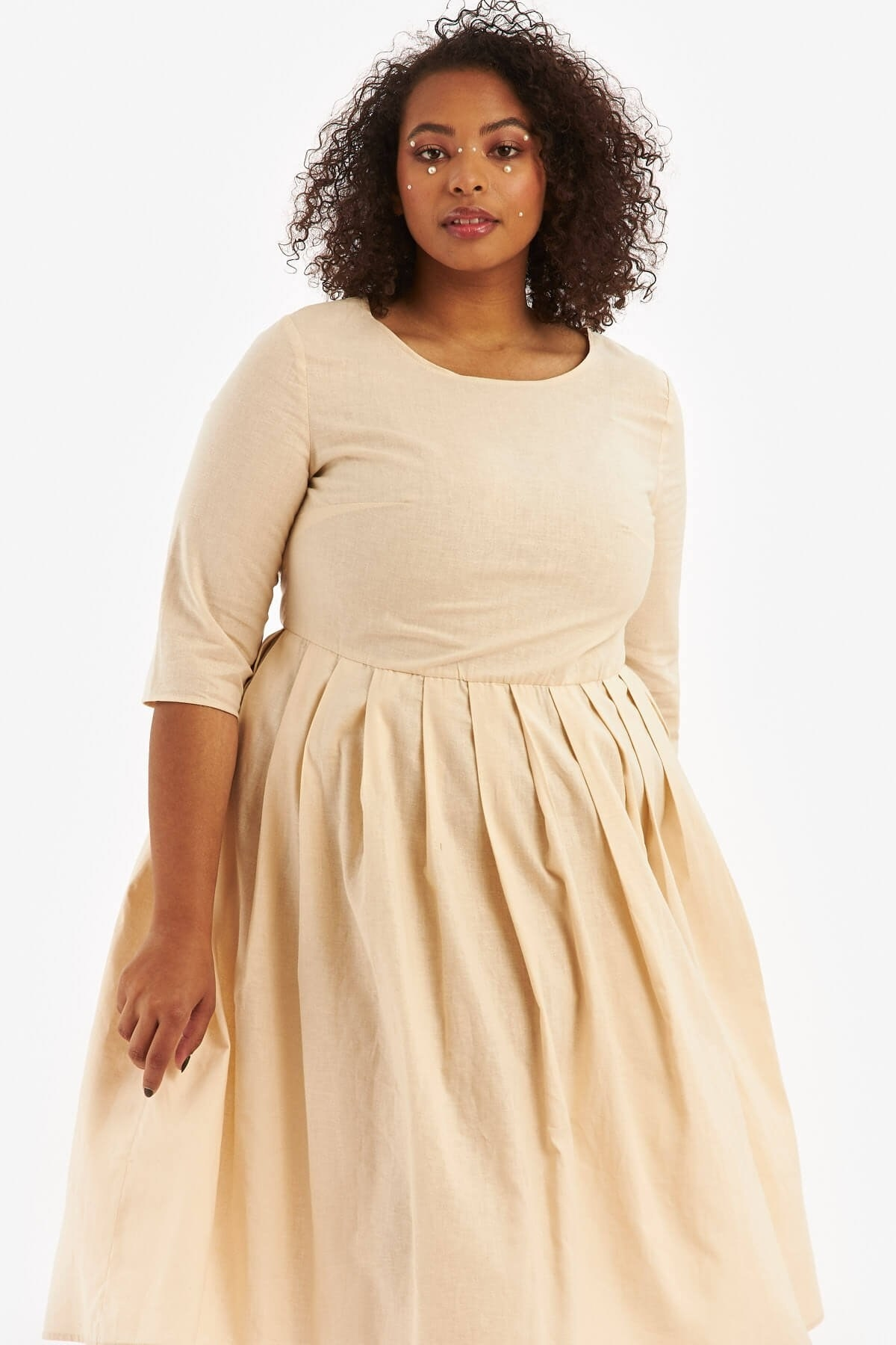 Model in a beige linen dress with 3/4 sleeves that cinches and tapers at waist