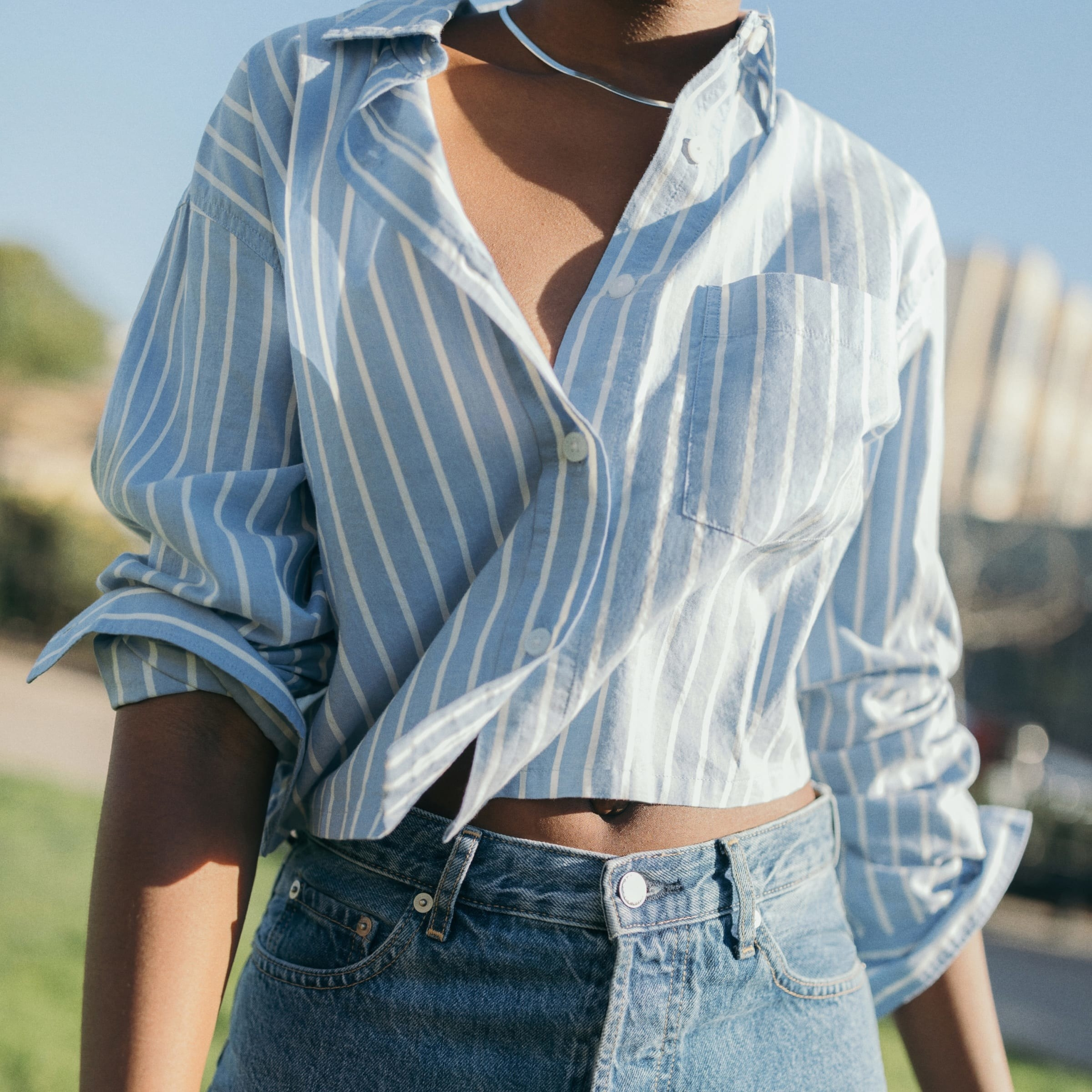 Model wearing the light blue and white vertical-striped shirt