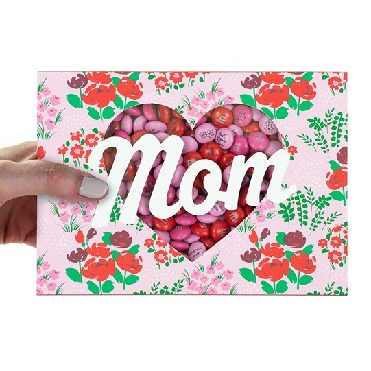 a floral box that says mom on it and has a heart cut out from the middle to reveal its filled with m&ms