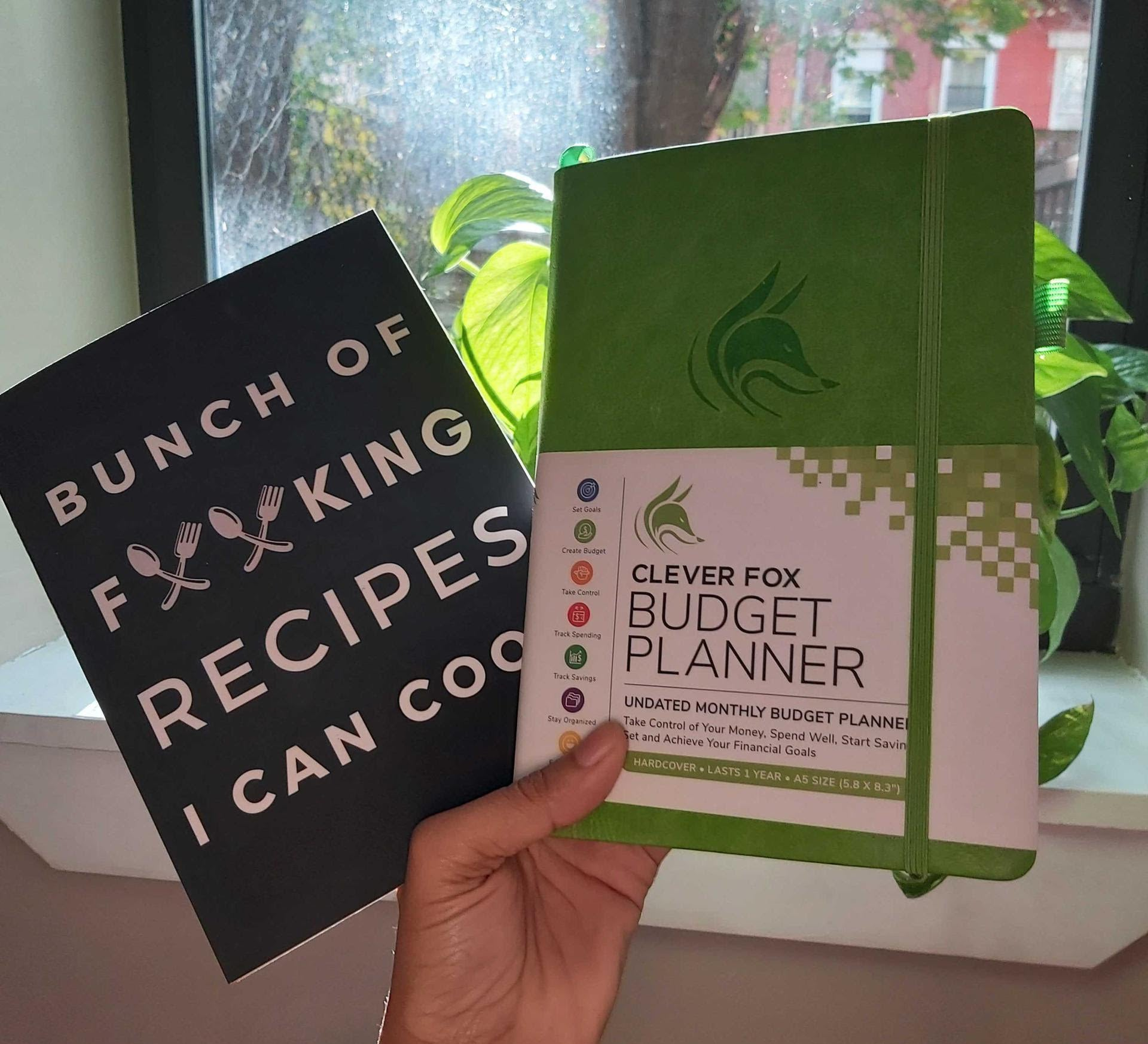 """buzzfeeder holding the budget planner and a recipe book that reads """"bunch of forking recipes I can cook"""" with forks in the middle of the word """"forking"""""""