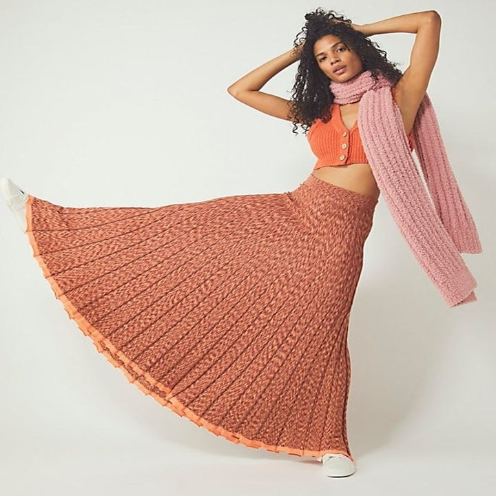 a model kicking their leg out to the side and wearing a knit maxi skirt, a scarf and a rib knit crop top